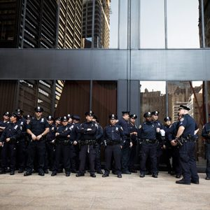 Group of police officers standing in front of glass windows.