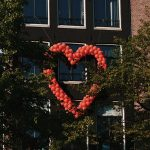 Red balloons in a heart shape on a building | Premium Pay Update