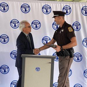 Deputy Noah Susick, Kalamazoo County Sheriff's Department shaking the hand of POAM President Tignanelli