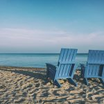 Two empty chair on the beach, facing the ocean. | Retirement With Adult Children