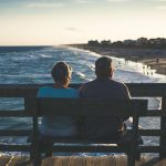 Couple sitting on the bench near an ocean | Retirement planning