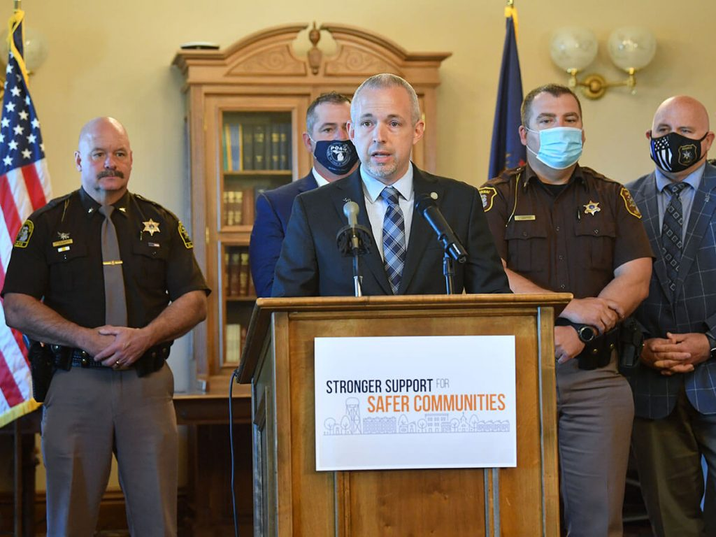 Michigan Speaker of The House Jason Wentworth speaking at a press conference with various law enforcement department heads standing behind him.   Training Plan to Support Local Police