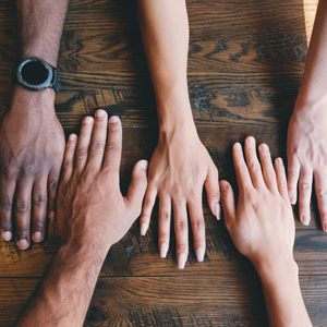 Four hands laying flat on a wooden table   New Member Groups